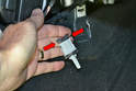 With the sensor out of the housing squeeze the two wiring harness clips (red arrows) together.