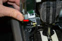 Push in the very small clip on the connection (red arrow) and pull the connection off the trim panel.