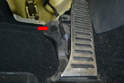 Use a small flathead screwdriver and remove the plastic cover (red arrow) on the accelerator pedal housing.