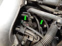 This picture shows the location of the two spark plugs accessible to the right of the intake manifold (green arrows).