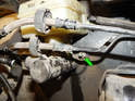 Loosen and remove the 13mm nut (green arrow) securing the right side of the master cylinder to the brake booster.