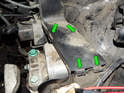 Carefully pry open the tabs (green arrows) on the cover to the cable routing tray just above the transmission mount.