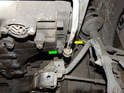Loosen and remove the 13mm bolt (green arrow) holding the power steering line (yellow arrow) to the transmission, and move the line out of the way.