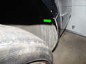 Left and Right Sides of car: Loosen and remove the T30 Torx screw (green arrow) holding the top edge of the bumper cover to the rear wheel liner.