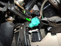 Shown here is the brake light switch mounted on the brake pedal assembly (green arrow).