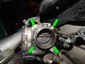 Loosen and remove the four bolts (green arrows) holding the throttle body to the intake manifold.
