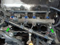 Loosen and remove the two 5mm hex bolts (green arrows) securing the fuel rail to the engine.