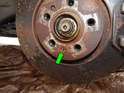The brake rotor is secured to the hub by a small Phillips head retaining screw (green arrow).