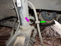 Pull the brake line grommet (green arrow) out of the retainer (purple arrow) on the front strut.