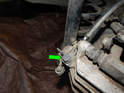 Loosen and remove the 13mm banjo bolt (green arrow) holding the brake line to the rear caliper.