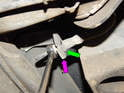 Pull out the retaining clip (purple arrow) and loosen the 11mm fitting while holding the opposite end (green arrow) with a 14mm wrench.