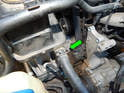 Use a pair of hose clamp pliers to slide back the hose clamp (green arrow) and then pull the line off.