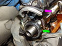 At the front of the cylinder head, pull the bearing cap (purple arrow) off and pop the camshaft seal (green arrow) off the camshaft.
