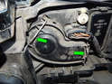 Left and Right Headlights: Use a screwdriver to pry back the retaining clips (green arrows) and remove the rear cover of the headlight assembly.