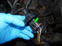 Left and Right Headlights: Pull back the locking tab (green arrow) on the electrical connector and pull it off the headlight bulb.