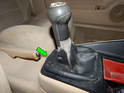 Press the rear (green arrow) of the gearshift housing to pop the shift boot trim ring out of the center console.