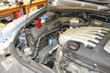 The air filter housing and air filter itself are located at the front right side of the engine compartment (red arrow).