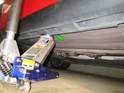 Both sides of car: Place the floor jack roughly in the center of the car along the body seam (green arrow).