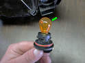 Both sides of car: Now press the old bulb (green arrow) in slightly and turn it to release from the bulb holder.