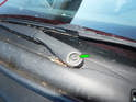 Now loosen and remove the two 13mm nuts (green arrow) holding each wiper arm to the wiper drive.