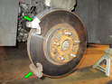Left and right sides: Removing the rotor requires removing the caliper-mounting frame (green arrows) from the rear of the wheel hub.