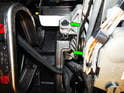 Loosen and remove the two 10mm bolts (green arrow) on the left side of the steering column.