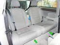 Lift the lower seat cushion up at the front edges (green arrows) until it releases.