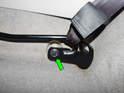 Loosen and remove the 13mm bolt (green arrow) holding the seat belt rail to the chassis.