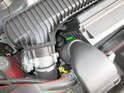 The oil filter housing is located between the air filter housing and the throttle body as shown here (green arrow).