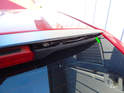 Begin by using a flathead screwdriver to carefully pry the top spoiler cover up and off the base plate (green arrow).