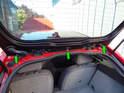Open the rear hatch and locate the three push clips that secure the rear of the spoiler cover to the car (green arrows).