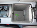 Open the center console rear compartment and locate the access panel at the bottom.