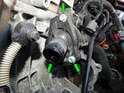 Loosen and remove the three 8mm bolts (green arrows) holding the cover on the thermostat housing.
