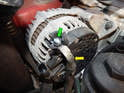 Loosen and remove the 13mm nut (green arrow) holding the positive terminal (yellow arrow) to the alternator.