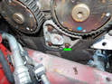 Loosen and remove the T30 Torx screw (green arrow) and pull the front timing belt cover off the engine.