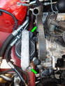 Loosen and remove the two 17mm bolts (green arrows) holding the cross brace and mount to the chassis.
