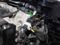 Follow the sensor's wiring harness up to the connector just right of the cylinder head (green arrow).