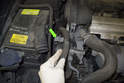 Then pull the power steering hose out of the mounting bracket (green arrow) and place aside.