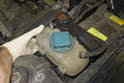 Unclip and slightly lift coolant and power steering reservoirs.