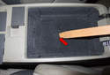 Working in the vehicle interior, open the center console storage compartment.