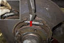 Next, unhook the lower return spring from the parking brake shoes (red arrow).