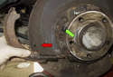Then remove the parking brake shoe together with the spring (red arrow), sliding it out of the mount (green arrow).