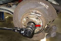 Using a 36mm socket, remove the wheel bearing fastener (red arrow).