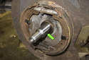 With the bearing removed, inspect and clean the spindle shaft (green arrow).