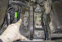 Replacing battery: Move the battery toward the right side of the vehicle to free it from the mount (green arrow).