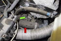 The crankshaft position sensor (green arrow) is located near the cylinder head, mounted in the transmission bell housing near the radiator hose (red arrow).