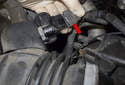 Working at the intake air boot between the throttle housing and intake air housing, disconnect the electrical connector (red arrow) by pressing the release tab and pulling the connector straight off.