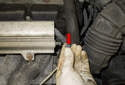 Working at the side of the fuel rail, remove the fuel pressure test port cap (red arrow).