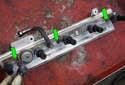 With the fuel rail on a bench, remove the three T25 Torx fasteners (green arrows).
