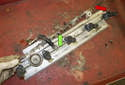 Then, remove the fuel injector locking plate (red arrow) from the fuel rail.